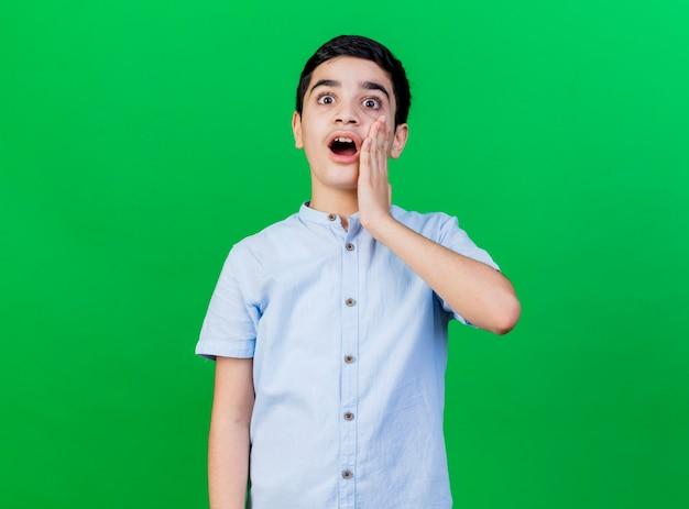 복사 공간이 녹색 배경에 고립 된 얼굴에 손을 유지하는 카메라를보고 놀란 어린 백인 소년