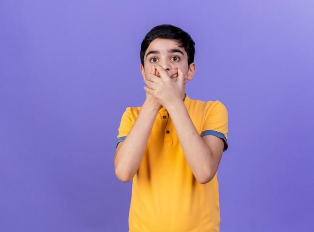コピースペースで紫色の背景に分離された口に手を置いてまっすぐに見て驚いた若い白人の少年
