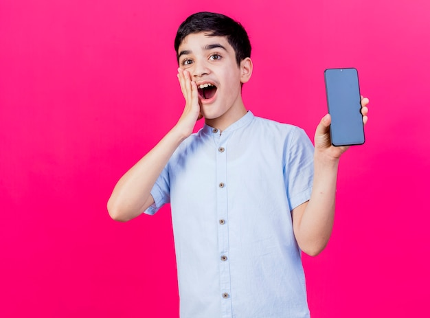 복사 공간이 진홍색 배경에 고립 된 얼굴에 손을 유지하는 카메라를보고 휴대 전화를 보여주는 놀란 젊은 백인 소년