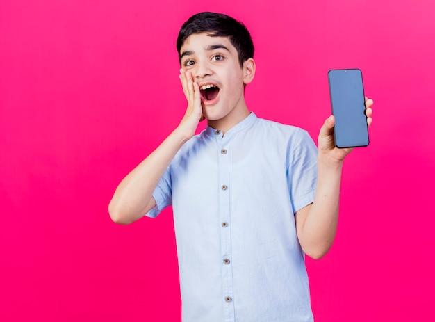 Giovane ragazzo caucasico sorpreso che mostra il telefono cellulare che guarda l'obbiettivo che tiene la mano sulla faccia isolata su fondo cremisi con lo spazio della copia