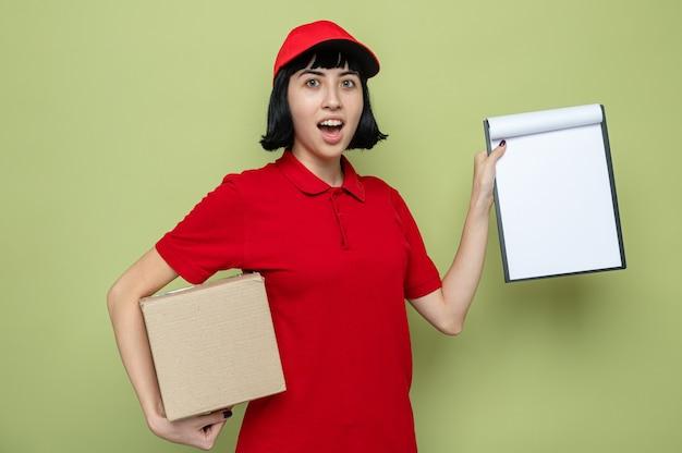 Giovane ragazza caucasica sorpresa delle consegne che tiene scatola di cartone e appunti