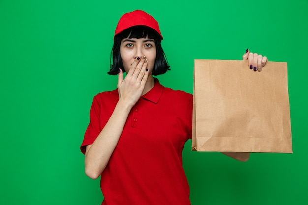 Surprised young caucasian delivery girl holding food packaging and putting hand on her mouth