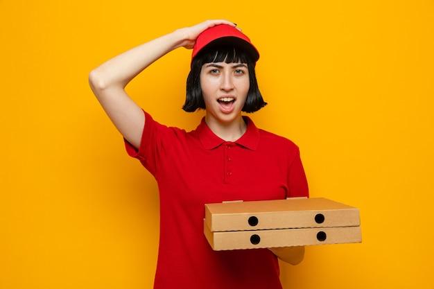Giovane ragazza caucasica sorpresa che tiene le scatole della pizza e le mette la mano sulla testa