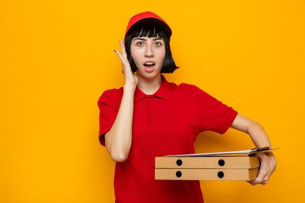 Sorpresa giovane ragazza caucasica delle consegne che si mette la mano sul viso e tiene in mano scatole per pizza