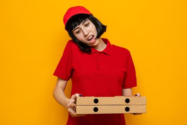 Giovane ragazza delle consegne caucasica sorpresa che parla al telefono tenendo le scatole della pizza