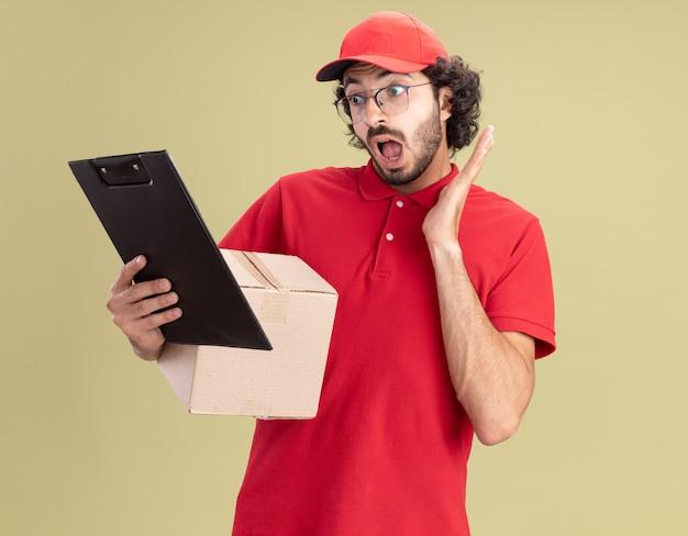 赤い制服とキャップを身に着けている驚いた若い白人配達人は、頭の近くに手を置いてクリップボードを見て、カードボックスとクリップボードを保持している眼鏡をかけています