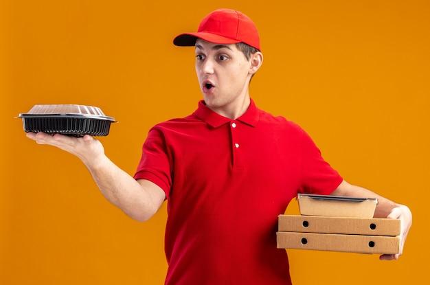 Sorpreso giovane fattorino caucasico in camicia rossa che tiene in mano scatole per pizza e guarda il contenitore per alimenti