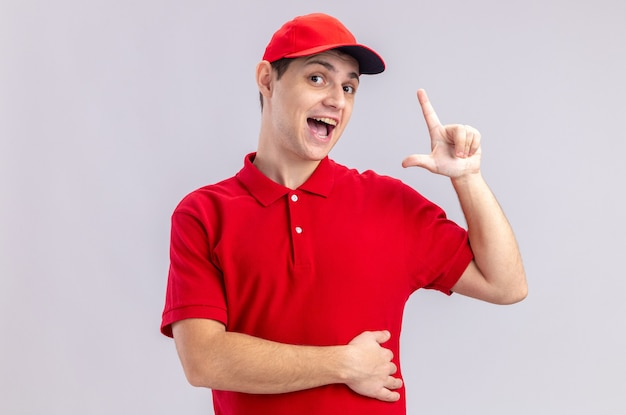 Sorpreso giovane fattorino caucasico in camicia rossa rivolta verso l'alto