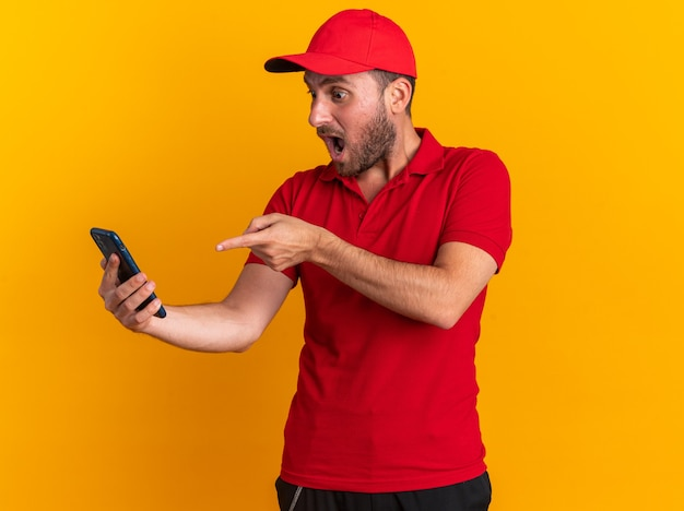 Surprised young caucasian delivery man in red uniform and cap holding looking at and pointing at mobile phone isolated on orange wall