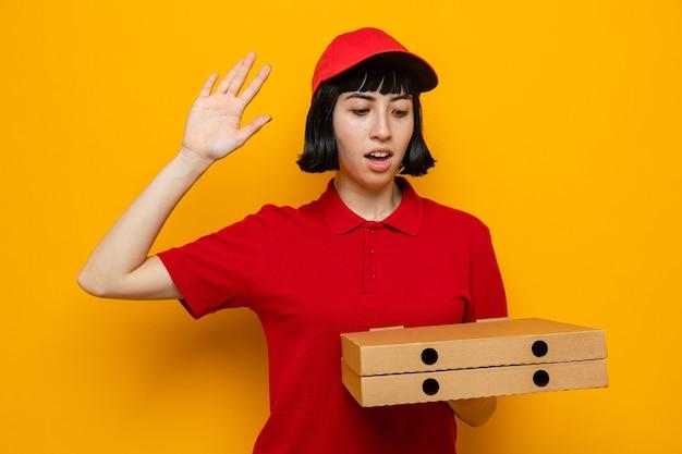 놀란 젊은 백인 배달 여성이 손을 들고 서 있는 피자 상자를 들고 보고 있다