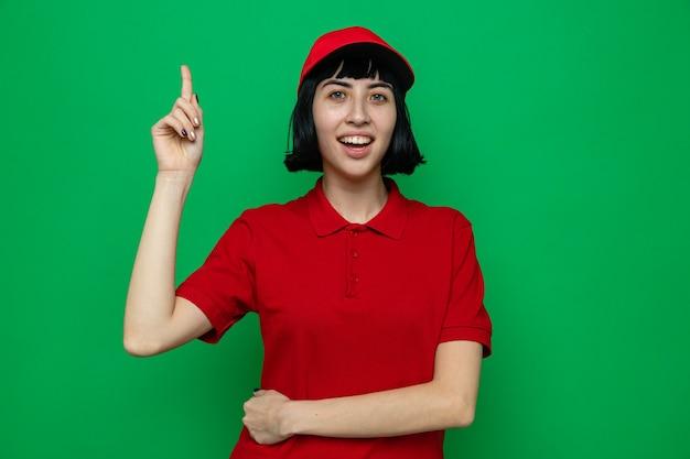 Giovane donna di consegna caucasica sorpresa che indica verso l'alto cercando