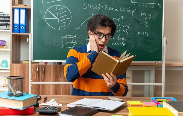 Sorpreso giovane insegnante di geometria caucasica con gli occhiali seduto alla scrivania con materiale scolastico in classe tenendo la mano sul libro di lettura del viso