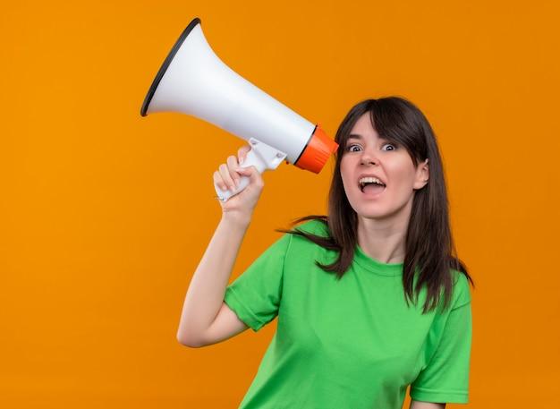 La giovane ragazza caucasica sorpresa in camicia verde tiene l'altoparlante e guarda la macchina fotografica su fondo arancio isolato