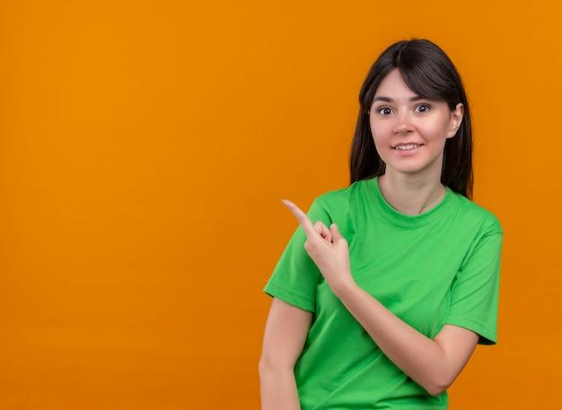 녹색 셔츠에 놀란 젊은 백인 여자 측면을 가리키고 복사 공간이 격리 된 오렌지 배경에 카메라를 찾습니다