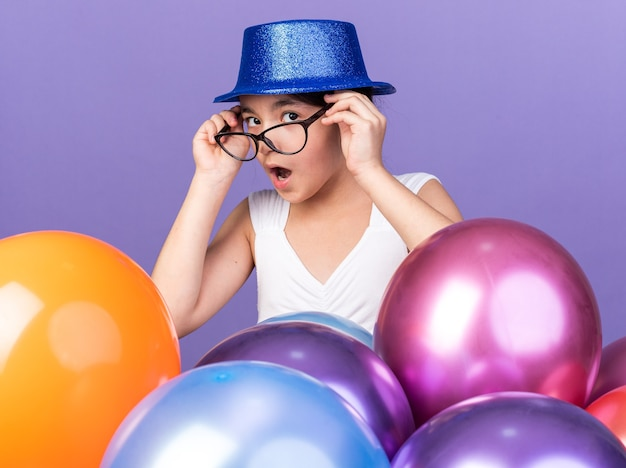 コピースペースと紫色の壁に分離されたヘリウム気球と立っている青いパーティーハットと光学ガラスで驚いた若い白人の女の子