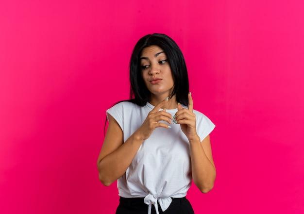 Giovane ragazza caucasica sorpresa guarda verso il basso rivolto verso l'alto con due mani isolate su sfondo rosa con spazio di copia