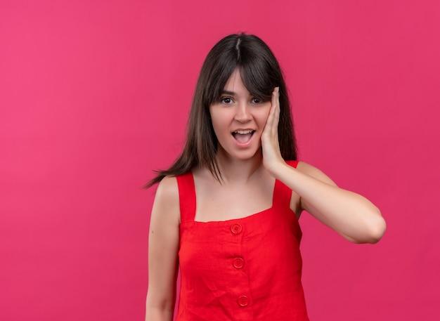 Удивленная молодая кавказская девушка кладет руку на лицо, глядя в камеру на изолированном розовом фоне с копией пространства