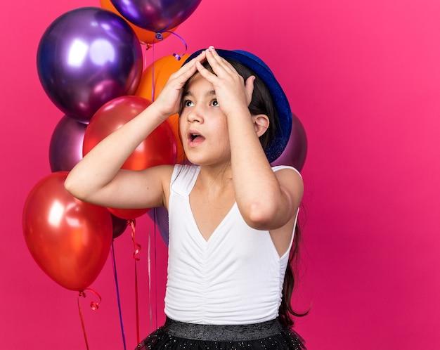 Sorpresa giovane ragazza caucasica mettendo le mani sulla testa e guardando in piedi davanti a palloncini di elio isolati sulla parete rosa con spazio di copia