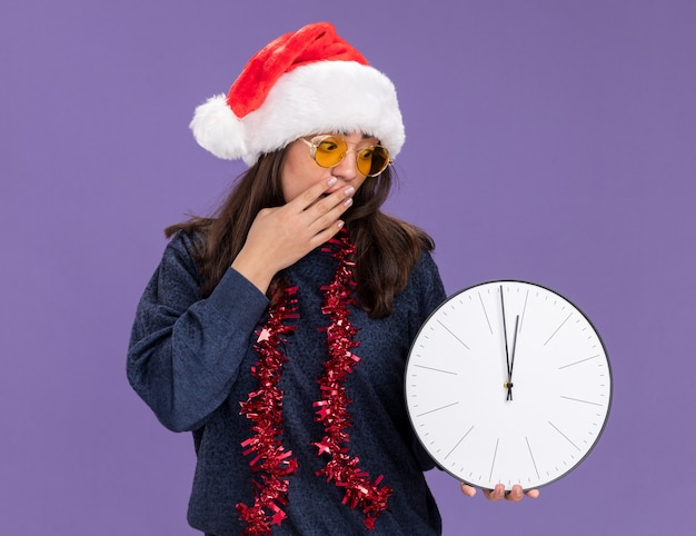 Sorpresa giovane ragazza caucasica in occhiali da sole con cappello da babbo natale e ghirlanda intorno al collo mette la mano sulla bocca tenendo e guardando l'orologio isolato sulla parete viola con spazio di copia