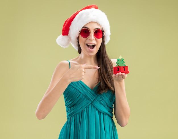 Giovane ragazza caucasica sorpresa in occhiali da sole con la holding del cappello della santa e che indica all'ornamento dell'albero di natale