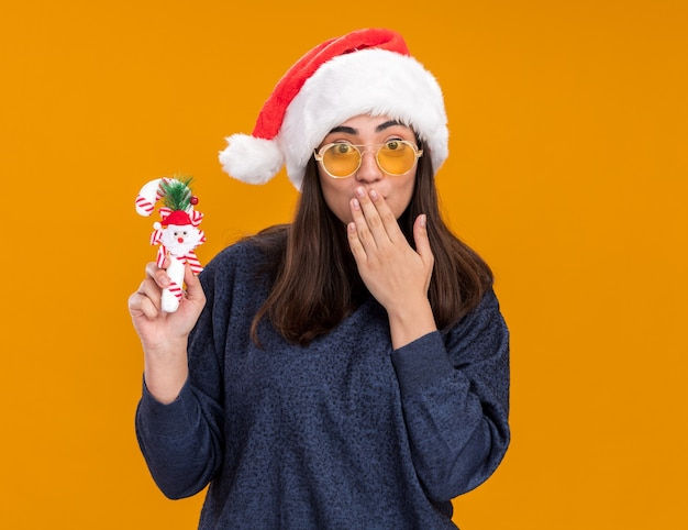 Surprised young caucasian girl in sun glasses with santa hat holds candy cane and puts hand on mouth isolated on orange wall with copy space