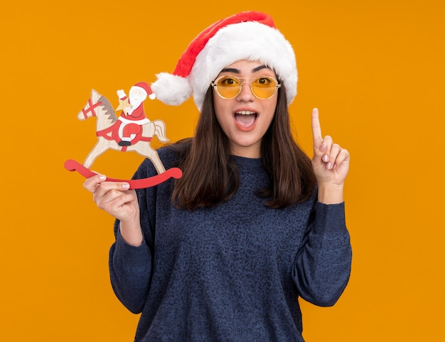 Surprised young caucasian girl in sun glasses with santa hat holds santa on rocking horse decoration and points up isolated on orange wall with copy space