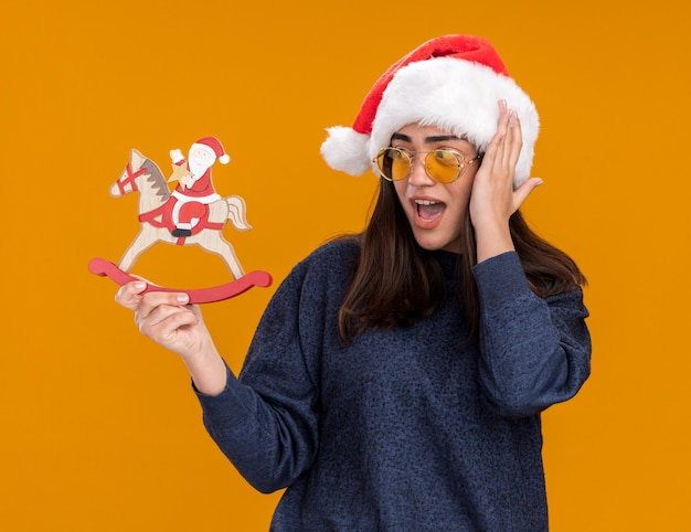 Surprised young caucasian girl in sun glasses with santa hat puts hand on head holding and looking at santa on rocking horse decoration isolated on orange background with copy space