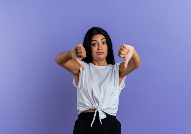 Удивленная молодая кавказская девушка показывает палец вниз двумя руками