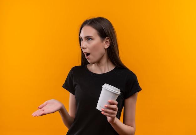 격리 된 오렌지 배경에 측면을보고 커피 한잔 들고 검은 티셔츠를 입고 놀란 젊은 백인 여자