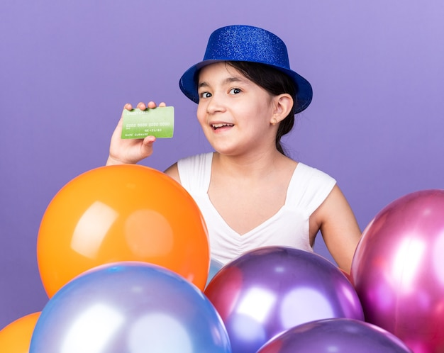 Surprised young caucasian girl wearing blue party hat holding credit card standing with helium balloons isolated on purple wall with copy space