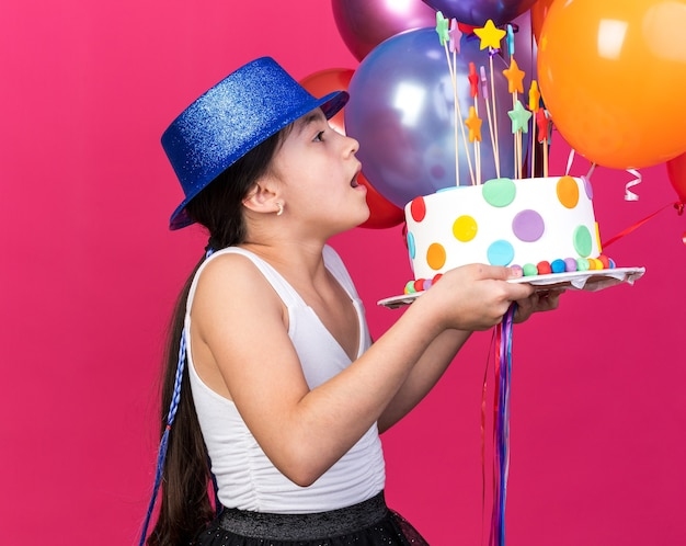 Surprised young caucasian girl wearing blue party hat looking at birthday cake and holding helium balloons isolated on pink wall with copy space