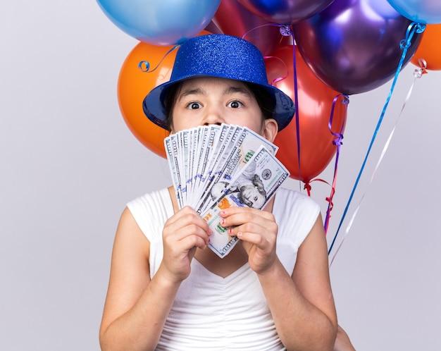 Удивленная молодая кавказская девушка в синей партийной шляпе, стоящая с гелиевыми шарами и деньгами, изолированная на белой стене с копией пространства