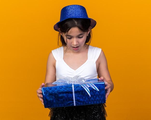 コピースペースでオレンジ色の壁に分離されたギフトボックスを保持し、見て青いパーティーハットで驚いた若い白人の女の子