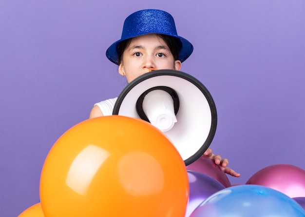 Surprised young caucasian girl with blue party hat holding loud speaker standing with helium balloons isolated on purple wall with copy space