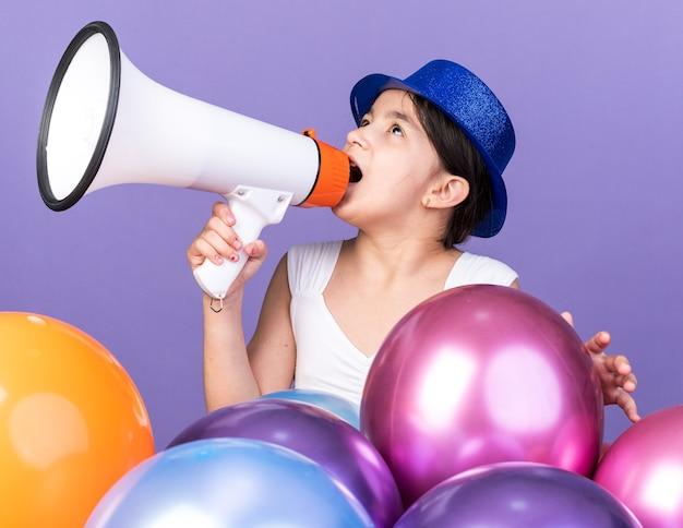 コピースペースと紫色の壁に分離されたヘリウム気球で立って見上げる大きなスピーカーに向かって話している青いパーティーハットで驚いた若い白人の女の子