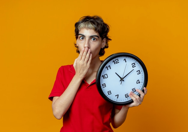 Удивленная молодая кавказская девушка с прической пикси держит часы и кладет руку на рот, изолированную на оранжевом фоне с копией пространства