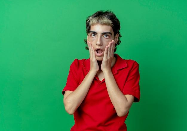 コピースペースで緑の背景に分離された顔に手を置くピクシーヘアカットで驚いた若い白人の女の子