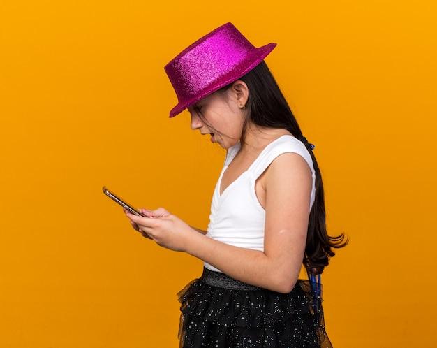 Удивленная молодая кавказская девушка с фиолетовой партийной шляпой, держащая и смотрящая на телефон, изолированную на оранжевой стене с копией пространства