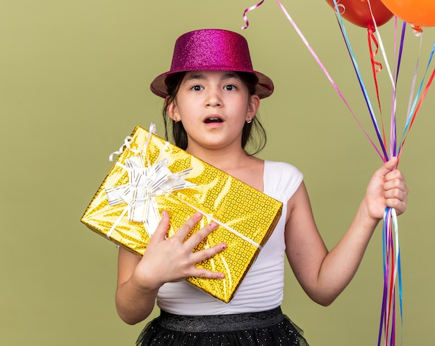 Surprised young caucasian girl with purple party hat holding helium balloons and gift box isolated on olive green wall with copy space