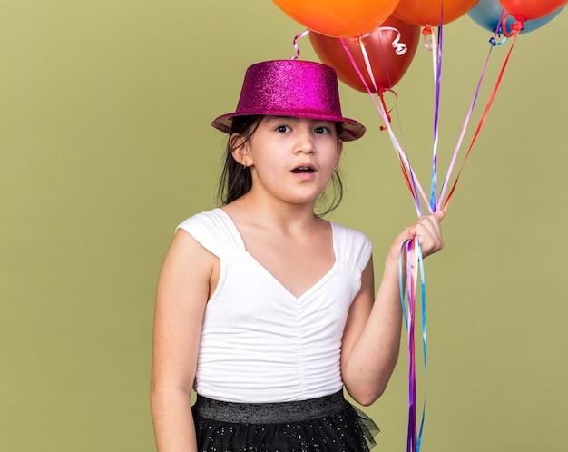 Удивленная молодая кавказская девушка с фиолетовой шляпой, держащая гелиевые шары, изолированные на оливково-зеленой стене с копией пространства