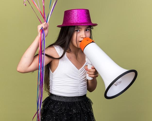 Sorpresa giovane ragazza caucasica con cappello da festa viola che tiene palloncini di elio e altoparlante isolato su parete verde oliva con spazio di copia
