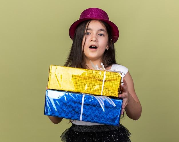 Удивленная молодая кавказская девушка в фиолетовой шляпе держит подарочные коробки, изолированные на оливково-зеленой стене с копией пространства