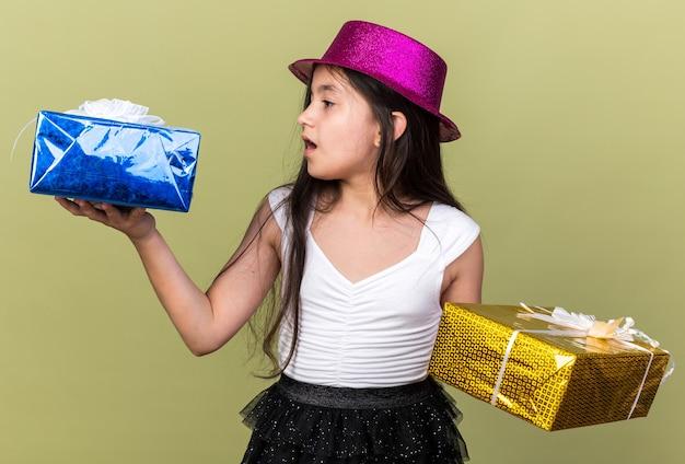 Giovane ragazza caucasica sorpresa con il cappello viola del partito che esamina le scatole regalo che tengono su ogni mano isolata sulla parete verde oliva con lo spazio della copia