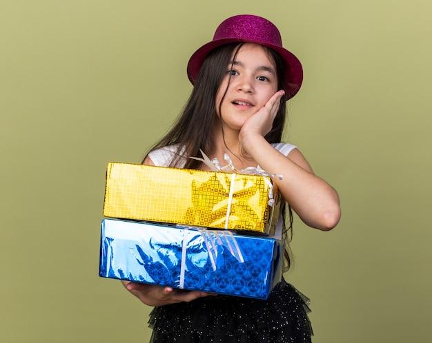 Sorpresa giovane ragazza caucasica con cappello da festa viola che mette la mano sul viso e che tiene i contenitori di regalo isolati sulla parete verde oliva con lo spazio della copia