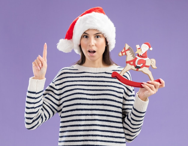 Surprised young caucasian girl with santa hat holds santa on rocking horse decoration and thumbs up isolated on purple wall with copy space
