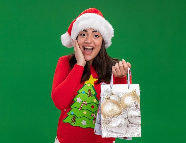 サンタの帽子をかぶって驚いた若い白人の女の子が顔に手を置き、コピースペースで緑の背景に分離された紙のギフトバッグを保持します。