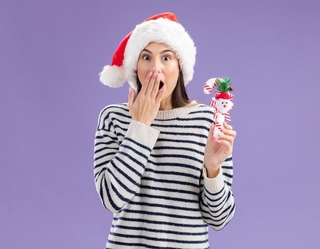 Удивленная молодая кавказская девушка в шляпе санта-клауса кладет руку на рот и держит конфету