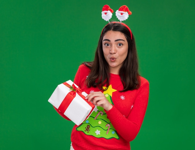 Surprised young caucasian girl with santa headband holds christmas gift box isolated on green wall with copy space
