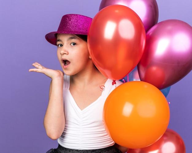 Giovane ragazza caucasica sorpresa con il cappello viola del partito che tiene i palloni dell'elio e che tiene la mano aperta isolata sulla parete viola con lo spazio della copia