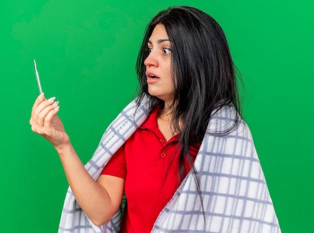 Giovane ragazza malata caucasica sorpresa avvolta in plaid che tiene e che esamina termometro isolato su priorità bassa verde